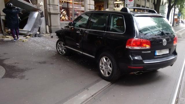 Im Vordergrund das Auto mit zerbeulter Front, im Hintergrund die eingedrückte Schaufensterscheibe und Gestalten in Motorradmontour, die durch das Fenster steigen.