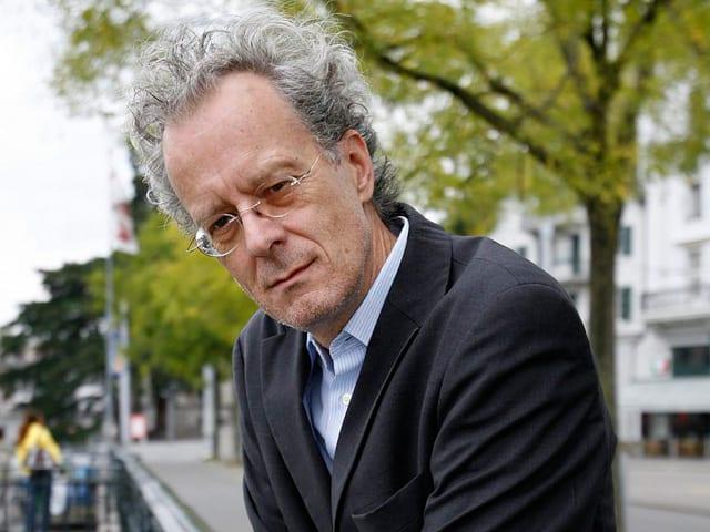 Ein Mann mit grauen Haaren und dunklem Kittel steht an einer Brücke.