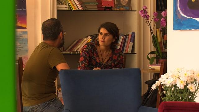 Galip Deniz Atinay mit einer ehemaligen Studentin im Café, blauer Sessel, Margeritenstrauss