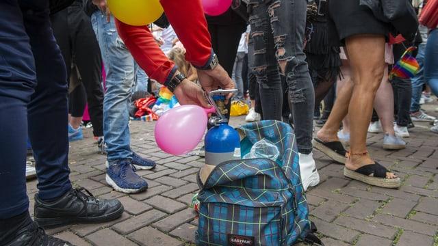 Eine Person füllt einen Ballon aus einer kleinen Gasflasche in einem Rucksack am Boden.
