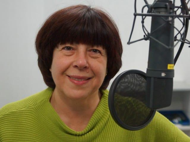 Frau mit grünem Pullover hinter Mikrofon.