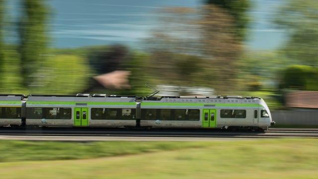 Ein BLS-Zug in voller Fahrt vor einem See.