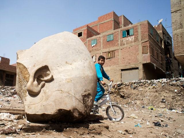 Teil einer Statue, Knabe fährt mit Fahrrad daran vorbei.