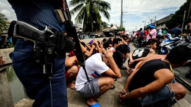 Ein Polizist steht bewaffnet vor Dutzenden von Männern, die auf dem Boden kauern.
