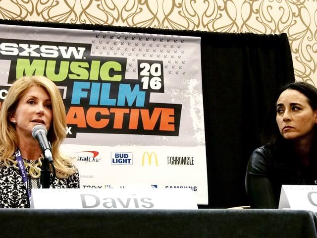 Zwei Frauen sitzen auf einem Podium an einem Tisch mit Mikrofonen.