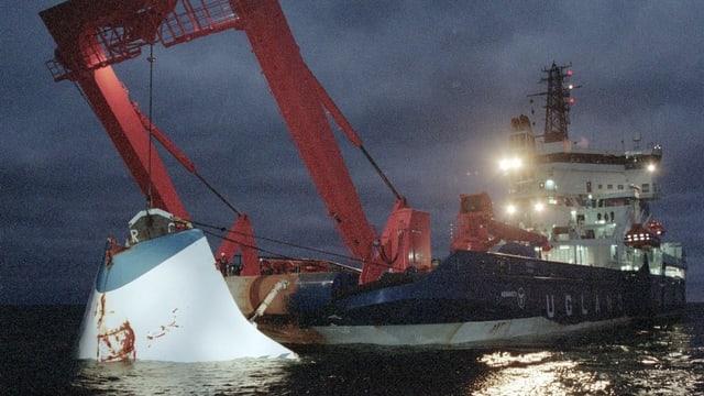 Ein Bergungsschiff hebt die Klappe aus dem Meer.