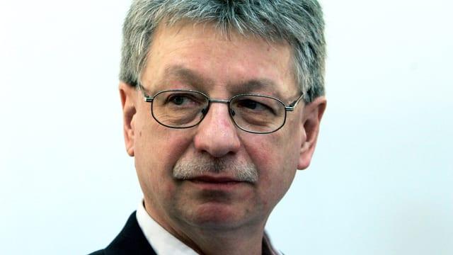 Ein Mann mit Brille und Schnauz; er schaut eher skeptisch.