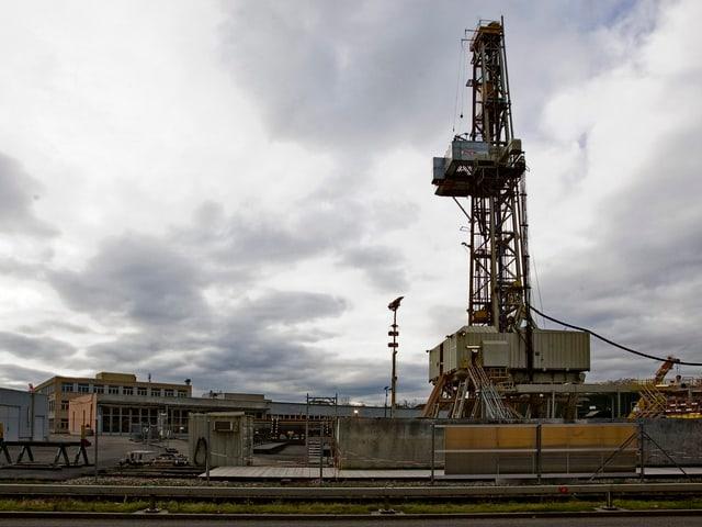 Ein Bohrturm in einer industriellen Landschaft.