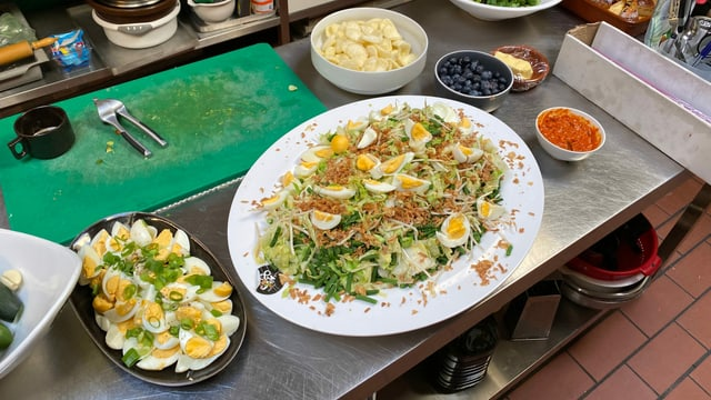 Auf einem Tisch stehen verschiedene Gericht aus Surinam, darunter Grünzeug und Eier.