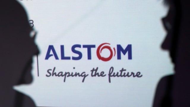 Silhouette von zwei Männern vor dem Alstom Logo