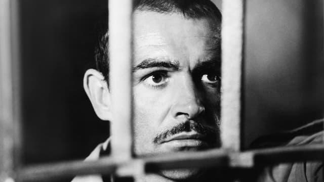 Filmszene: Gesicht eines Mannes hinter Gittern.