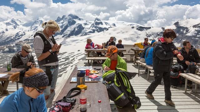 Terrasse der Hörnlihütte am Matterhorn: Eine Restaurant-Angestellte nimmt die Bestellung auf; im Hintergrund Kleines Matterhorn und Monterosa-Massiv.