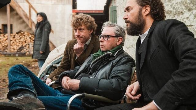 Drei Männer unterschiedlichen Alters sitzen an einem Filmset und blicken konzentriert drein.