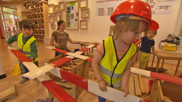 Kinder in Baustellen-Kleidung.