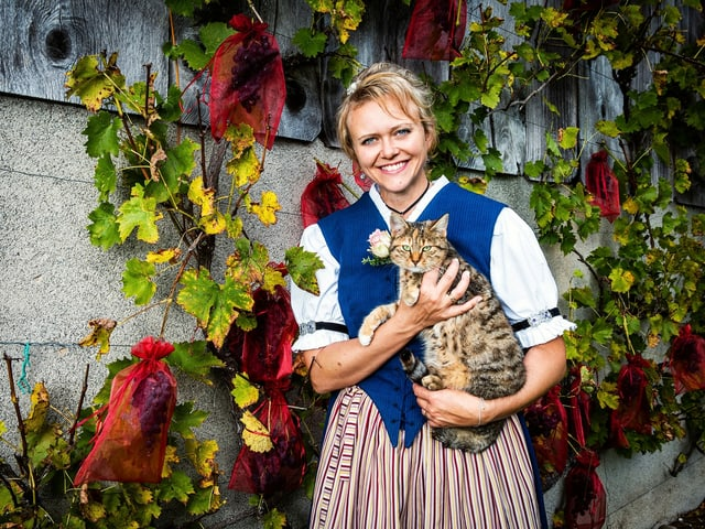Brigitte steht vor einer rebenbewachsenen Mauer. Sie hält eine Tiger-Katze im Arm.