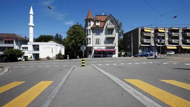 Bild einer Kreuzung und 3 Häusern an der Strasse. Ein weisses 2 Stockwerke hohes Blockgebäude mit einem ca. 13m hohen Minarett turm