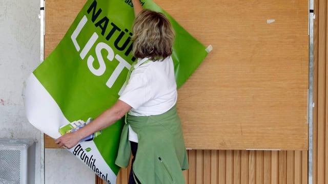 Eine Frau hängt ein Plakat der Grünliberalen nach einer Generalversammlung ab.