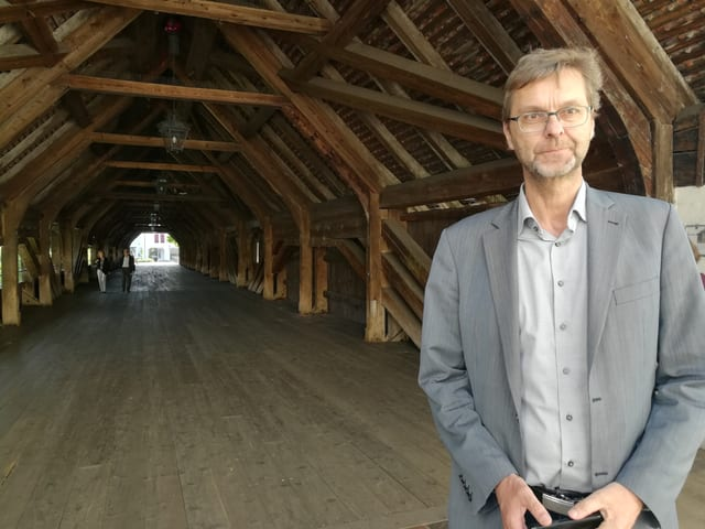 Mann in Anzug auf alter Brücke.