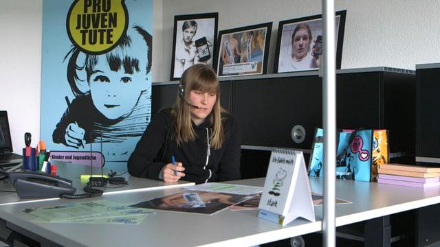 Moana Crescionini von der Pro Juventute-Beratungsstelle sitzt an ihrem Arbeitsplatz mit Headset auf dem Kopf.