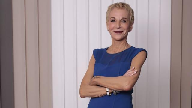 Margrit Stamm eine blonde kurzhaarige Frau in blauem Kleid. Schlank.