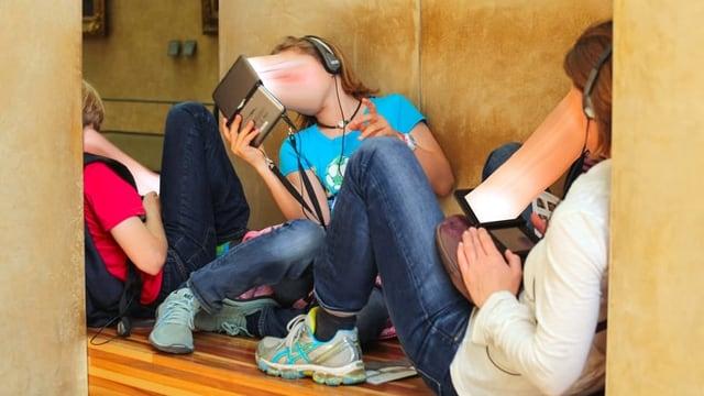 Jungendliche sitzen am Boden und Blicken in Smartphones.