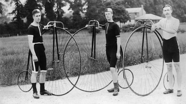 Drei Besitzer eines Penny Farthings posieren in Radler-Outfit und mit ihren Rädern.