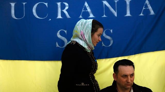 Ein Mann und eine Frau vor einer ukrainischen Fahne.