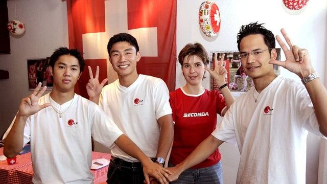 Drei Männer und eine Frau posieren vor einer Schweizer Fahne.