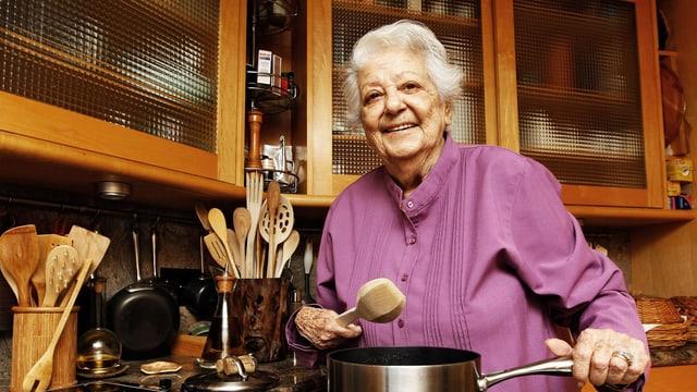Eine ältere Frau steht am Herd und kocht