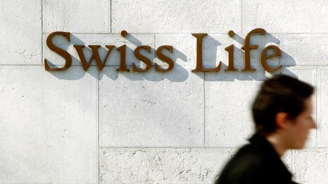 Emblem der Lebensversicherung «Swiss Life» an weisser Wand in Zürich. Eine Passantin schreitet daran vorüber.