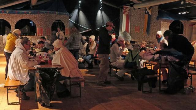 Chesslete-Fasnächtler auf Festbänken im Festzelt