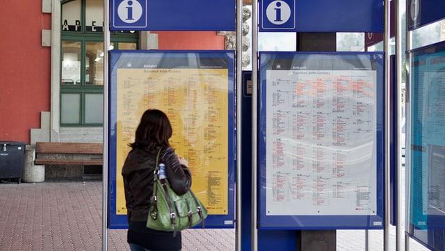 Eine Frau studiert den Fahrplan auf einem Bahnhof.