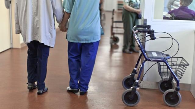 Pflegerin führt Patient, daneben steht ein Rollator