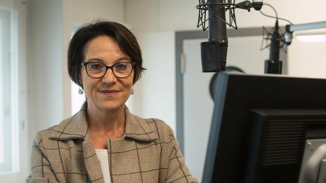 Eine Frau mit Brille am Mikrofon.