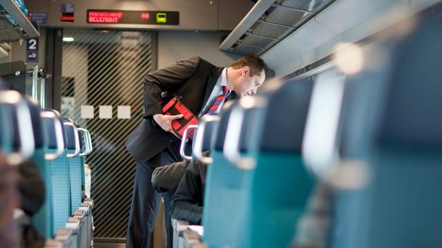 In conductur controllescha ils bigliets da passagiers en in tren da las Viafiers federalas.