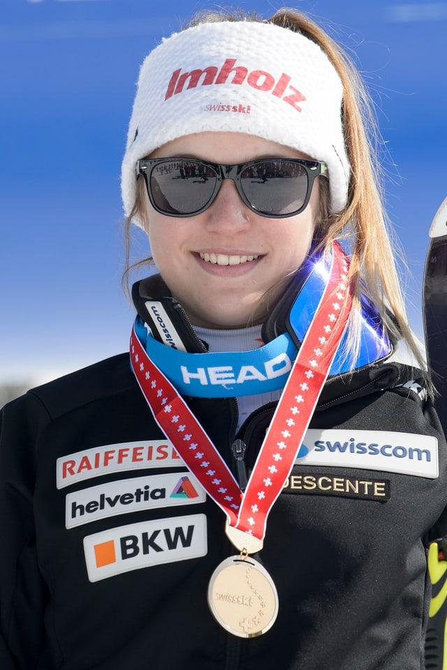 Vanessa Kasper cun egliers da sulegl e medaglia enturn culiez.