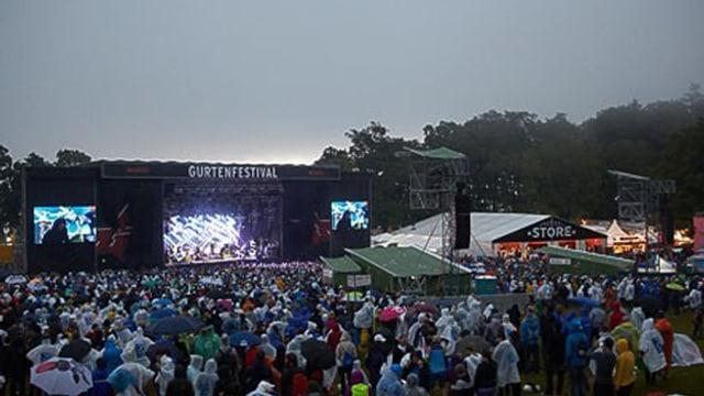 Die Hauptbühne des Gurtenfestival mit schwarzem Himmel und Besuchern in Regenschützen.