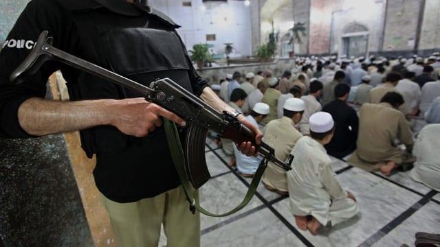 Ein Mann mit einem Maschinengewehr bewacht betende Muslime.