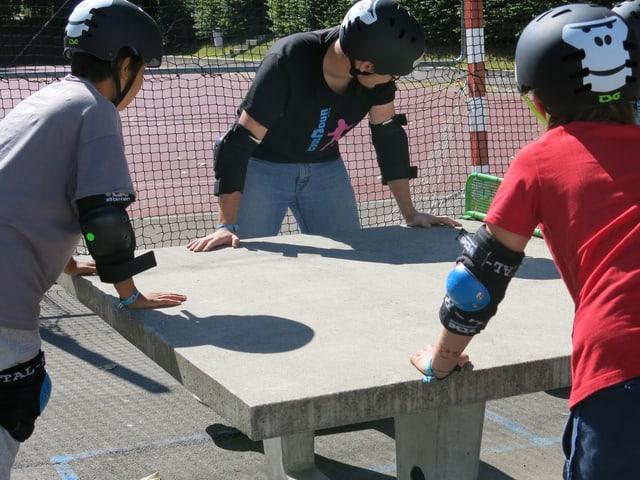 Jugendliche auf Skateboards rund um einen Pingpong-Tisch.