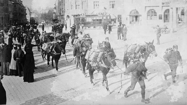 Soldaten mit Pferden gehen über einen Platz, an dessen Rändern Passanten stehen.