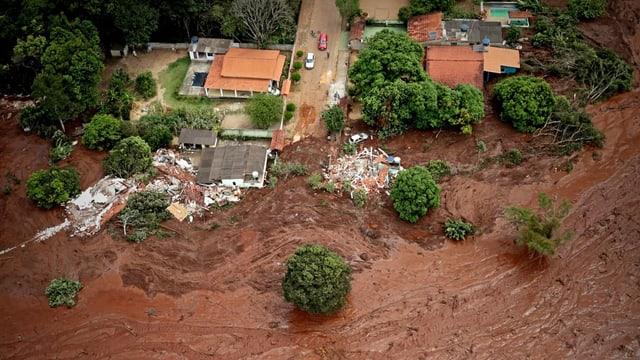 Zerstörte Häuser umspült von Schlammmassen.