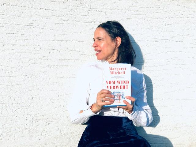 Annette König hält den Roman «Vom Wind verweht» von Margaret Mitchell in der Hand. Sie trägt im Look des 19. Jahrhunderts eine weisse Rüschenbluse und einen blauen Samtjupe.
