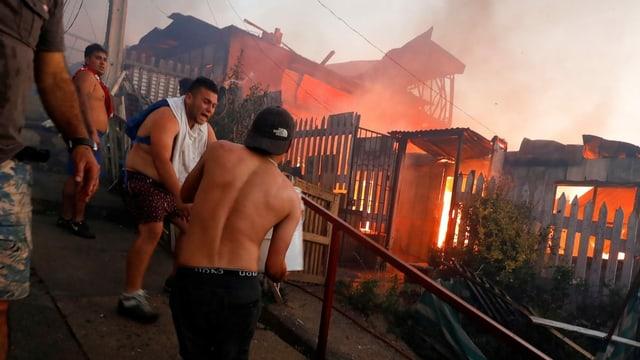 Männer an einem brennenden Gebäude.