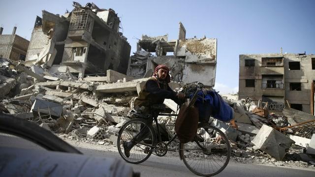 Einbeiniger Mann mit Turban fährt vor zerbombten Häusern mit dem Velo vorbei.