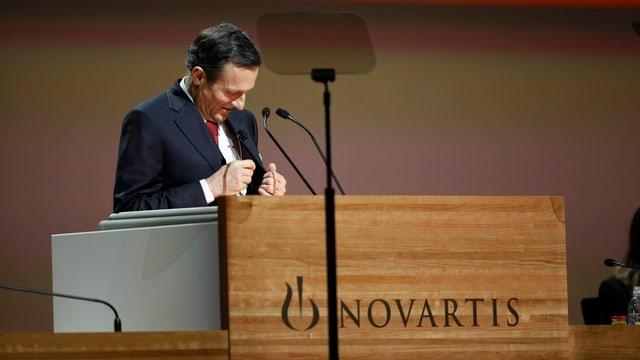 Daniel Vasella an einem Rednerpult. Er nestelt an seinem Veston rum.
