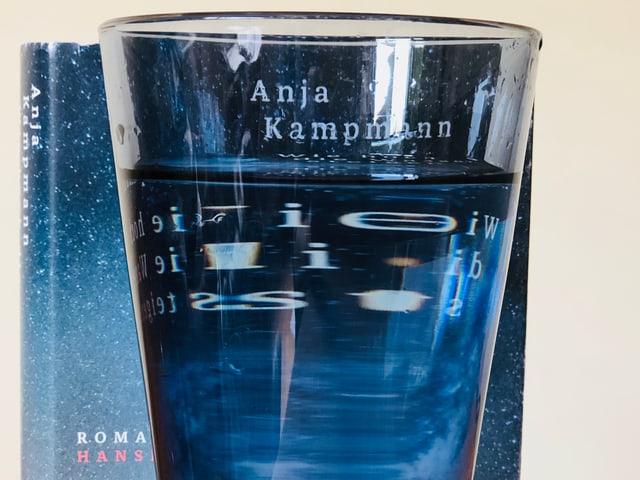 Der Roman «Wie hoch die Wasser steigen» steht hinter einem gefüllten Wasserglas. Die Schrift des Buchtitels ist leicht verschwommen.