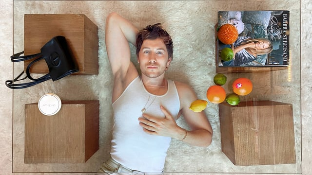 ein Mann liegt auf dem Boden, umgeben von Tischen mit Früchten, Taschen und Magazinen drauf