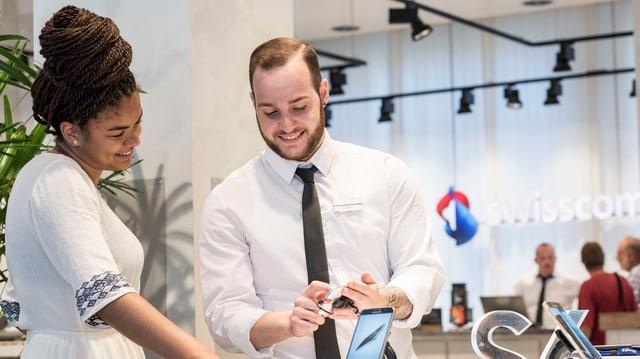 Zwei Swisscom-Angestellte sehen lächeln ein Mobiltelefon an