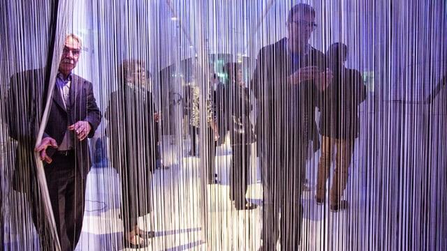 Der Eintritt in die Ausstellung verbirgt sich hinter einem Vorhang aus hängenden Fäden.