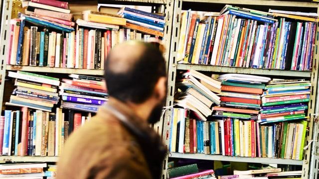 Mann vor einem vollgestopften Buchregal